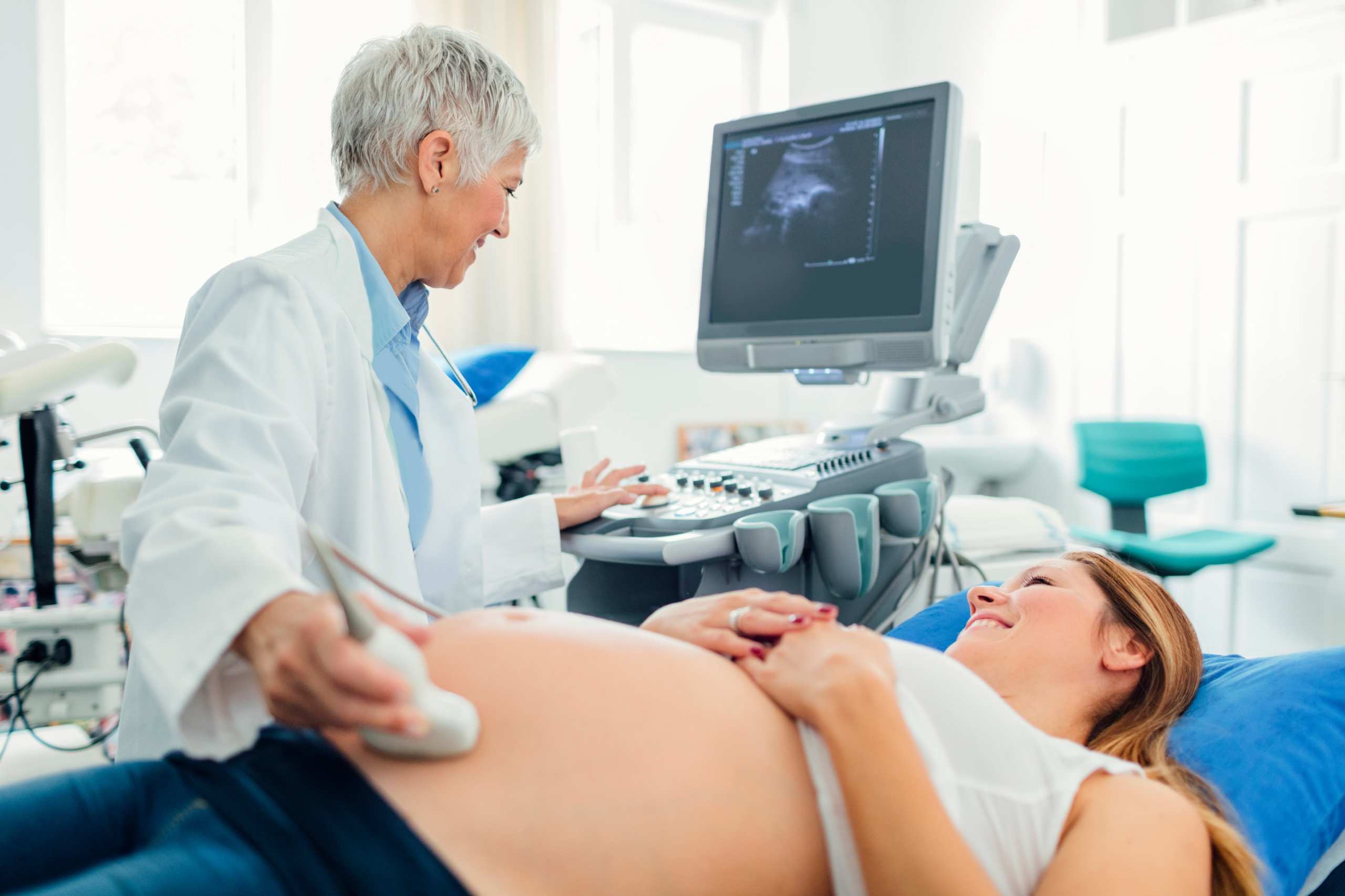 Pregnant woman and her male doctor in a consultation. Woman lying down while her doctor doing ultrasound examination. Young woman looking at her doctor.