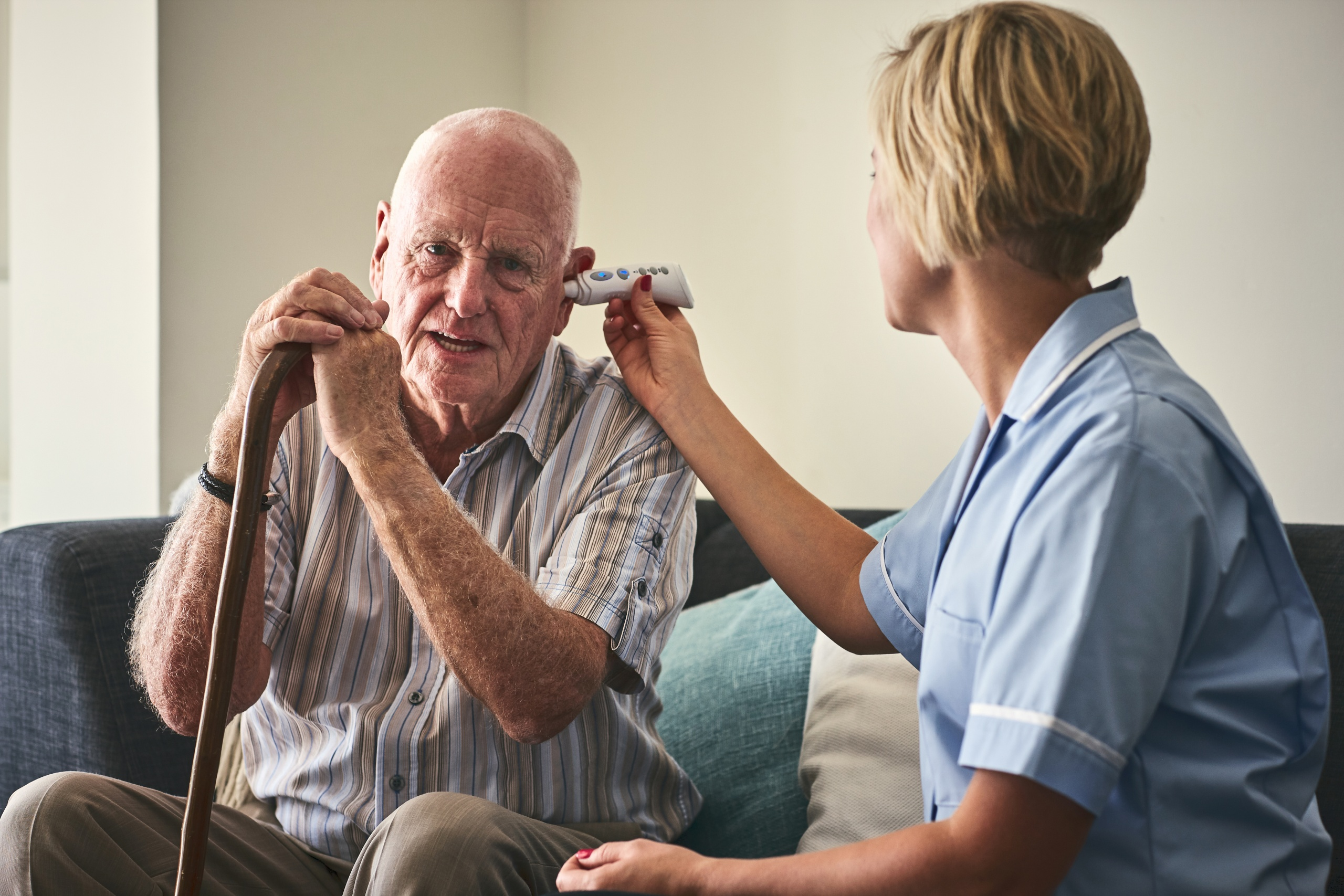Female nurse checking patient temperature while sitting on sofa at care home