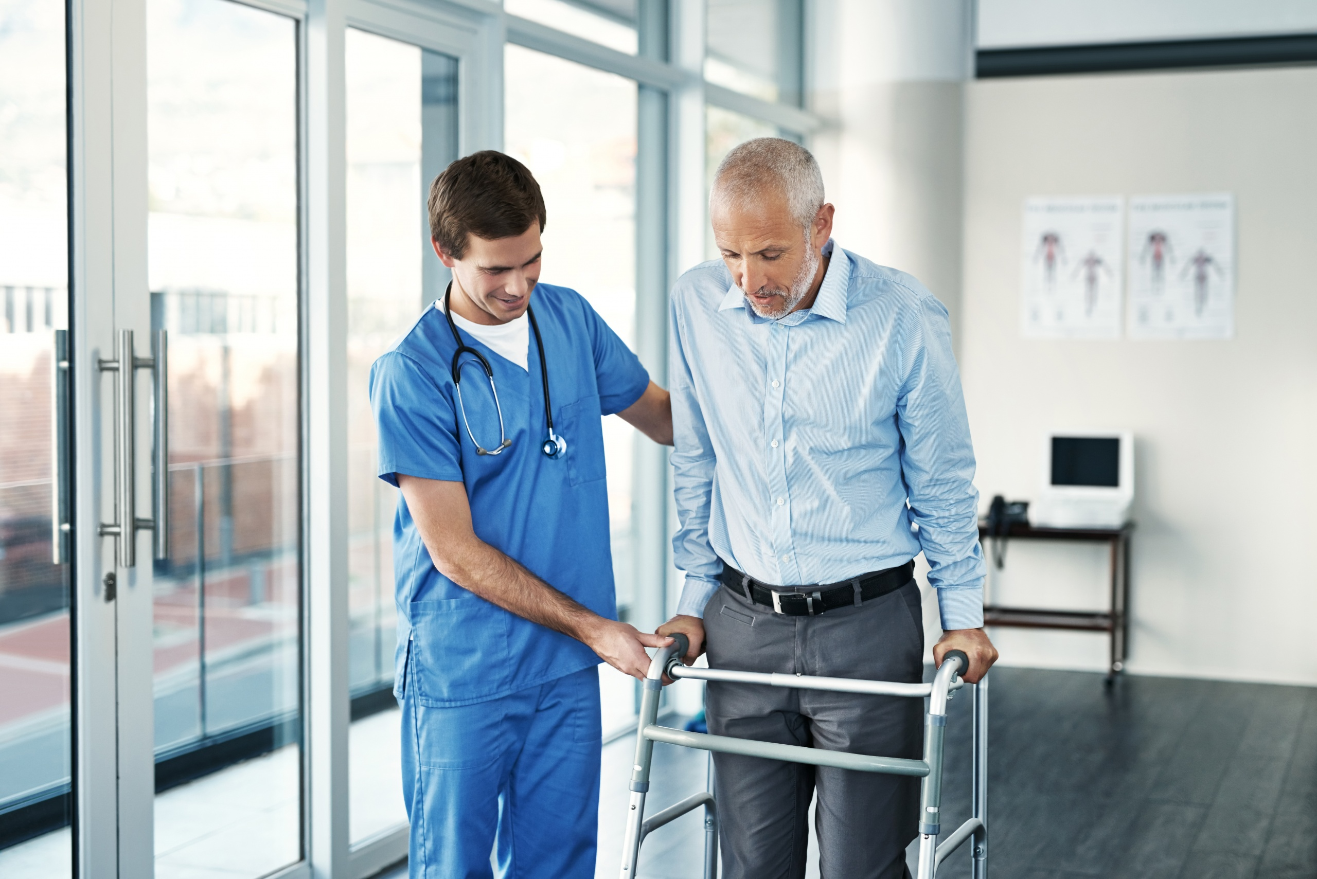 Shot of a male nurse assisting a senior patient with a walker
